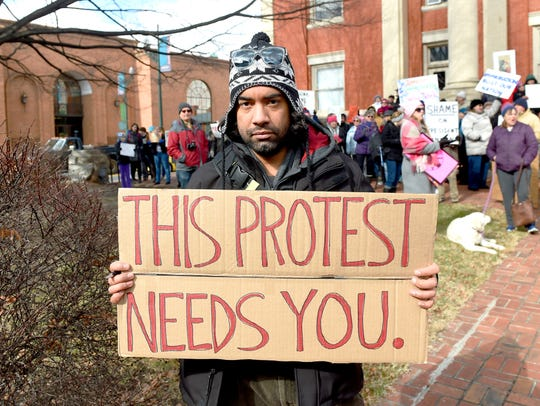 Aaron Barmer of Staunton holds up a sign that reads,