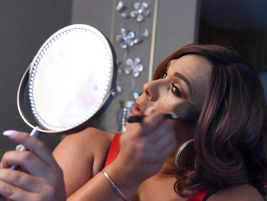 Chyna Black looks into a mirror as she applies makeup
