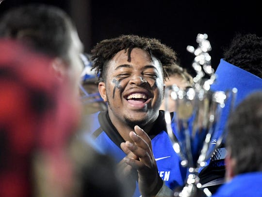 Robert E. Lee's Dee Chisley shows his excitement as the team receives the championship trophy after they defeated Luray in the Region 2B championship football game played in Staunton on Friday, Nov. 24, 2017.