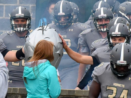 Players reach out to touch the hive that represents
