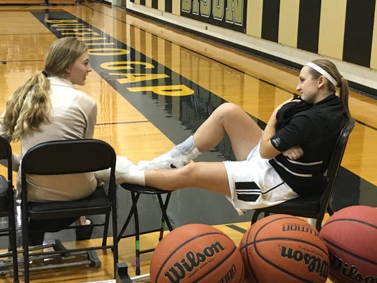 Hannah Varner, left, talks with friend and teammate Marybeth Strickler during Buffalo Gap's basketball game Wednesday, Dec. 20. Varner is out for the season with an ACL injury.