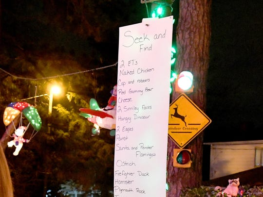 A seek and find challenge hangs among holiday lights and decorations, challenging visitors to find as many items on the list as they can from the mass of decorations that fill the lawns in front of both houses at 9604 and 9606 Asbury Court in Henrico.