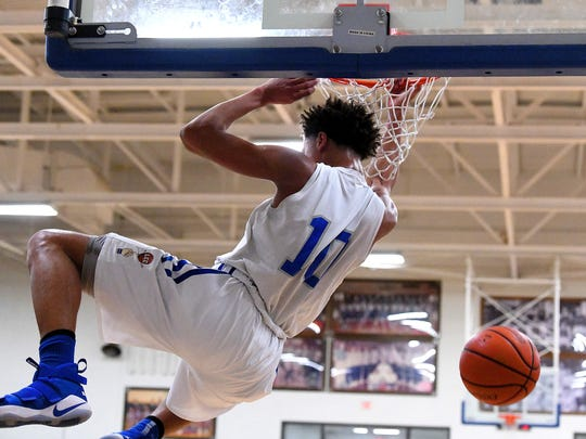 Robert E. Lee's Jarvis Vaughan scores a little hang time after slamming the ball through the basket during a basketball game played in Staunton on Tuesday, Jan. 9, 2018.