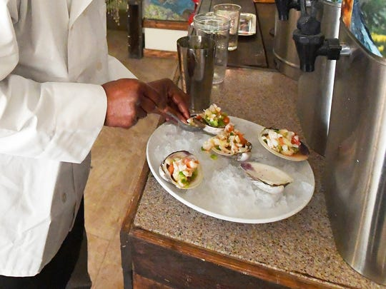 Co-owner Jerome Dericho plates conch ceviche for a reporter to taste during an interview at Island Sol Cafe, located at 302 North Central Avenue in Staunton.