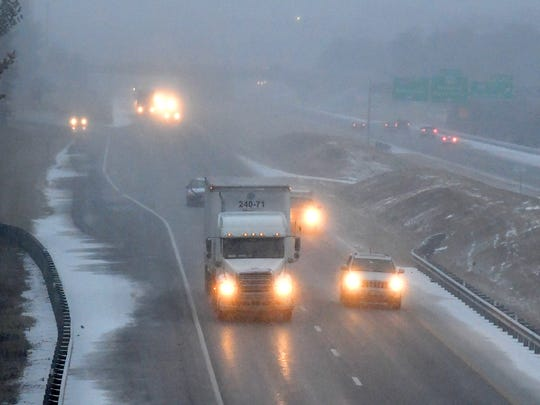 Snow falls as traffic flows south on Interstate 81 near the Interstate 64 interchange at Staunton on Wednesday, Jan. 17, 2018.