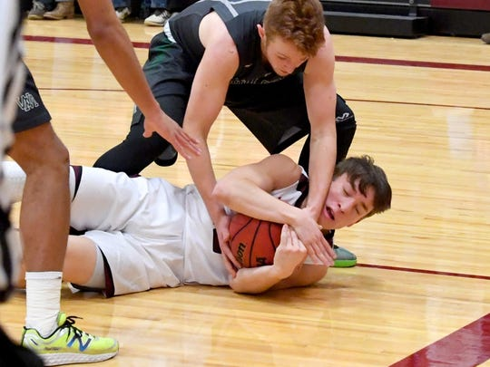 Stuarts Draft's Nick Lasam protects the ball after diving after a loose ball during a basketball game played in Stuarts Draft on Tuesday, Jan. 30, 2018.
