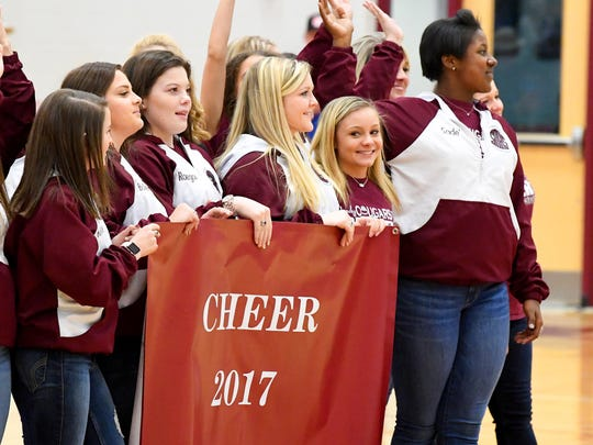 The Stuarts Draft competition cheer team shows their new 2017 state championship cheer banner to the crowd between the girls and boys basketball games played in Stuarts Draft on Tuesday, Jan. 30, 2018.