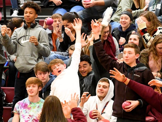 Spectators stretch to try and catch mini basketballs and water bottles being tossed to them as giveaways before the start of the boys basketball game played in Stuarts Draft on Tuesday, Jan. 30, 2018.