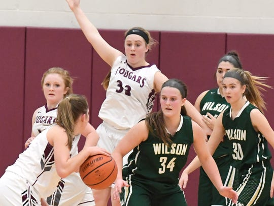 Stuarts Draft's Alexi Bridge goes high to signal she's open as Wilson Memorail's Cheridan Hatfield (center) guards against the ball carrier during a basketball game played in Stuarts Draft on Tuesday, Jan. 30, 2018.