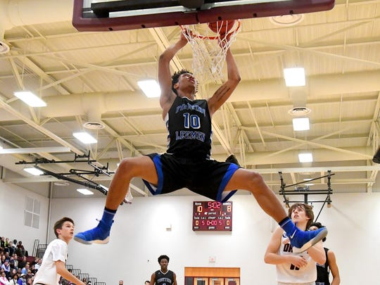 Robert E. Lee's Jarvis Vaughan holds onto the rim a