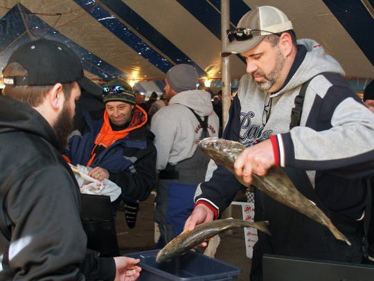 Brian Mahlendorf switches fish being weighed at the