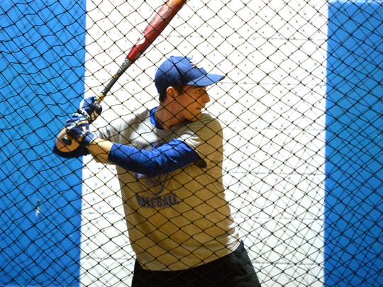 Sam Hill, a Fort Defiance junior who has Wilson Disease, prepares to take a swing Monday in the school's auxiliary gym on the first day of baseball practice.