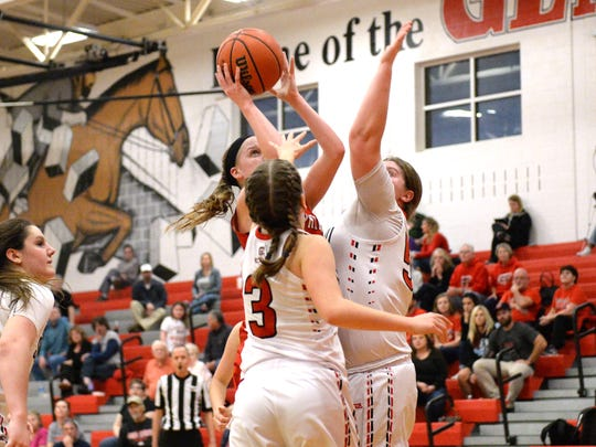 Riverheads' Sara Moore tries to get a shot over two Stonewall defenders Wednesday in a Region 1B semifinal game. Stonewall won 55-50.