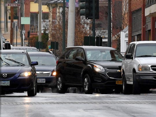 A motorist (center) heads front first into an available parking spot on West Beverley Street in downtown Staunton.