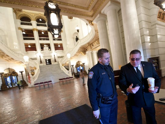 Bill Kohler, right, shares a photograph of his son, Ayden Zeigler-Kohler, with Nick Finicle of the Capitol Police in the atrium of the Capitol in Harrisburg. Kohler was visiting with senators about House Bill 407 to help raise funds for pediatric cancer research.