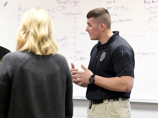 Officer Tyler Miller (right) of the Staunton Police Department works to appropriately respond to an encounter with a person, portrayed by a CIT trainer, who is found walking the white line of a road. It is part of a role-play exercise during Crisis Intervention Team (CIT) training held in Staunton on March 7, 2018.