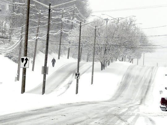 A pedestrian walks in the snow alongside Richmond Road
