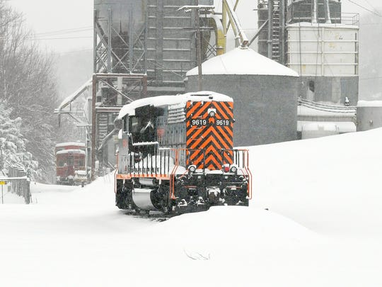 A locomotive sits on snow-covered tracks near Statler
