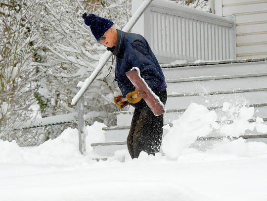 A man shovel's snow from on front of a residence on