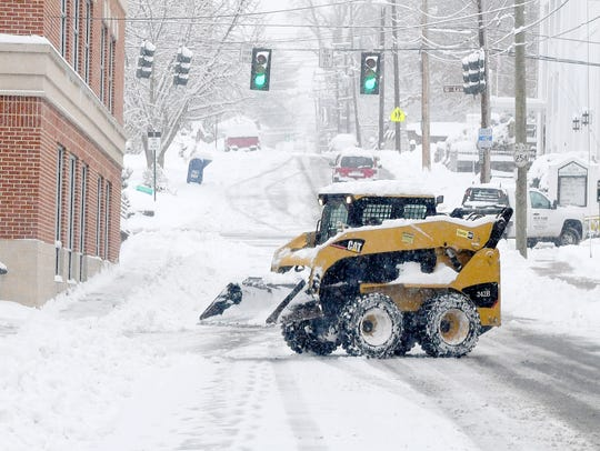 A skid steer loader is used to remove snow from around