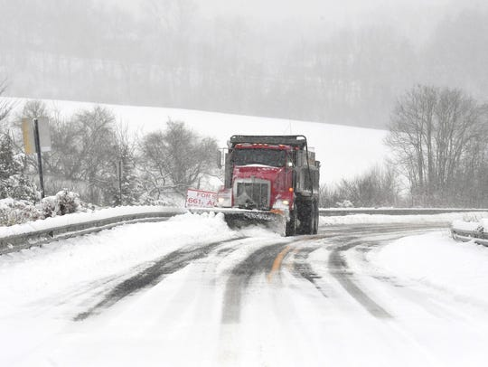 A snowplow clears Barterbrook Road during a spring