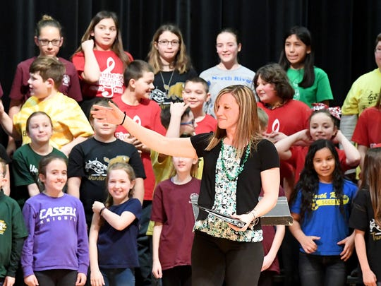Music specialist Sarah Stoll from Wilson Elementary, one of several working with the choir, directs the audience to applause for the students of the Augusta County Elementary Honors Choir after they perform a song she led on stage at Stuarts Draft High School on March 16, 2018. The choir consisted of students from Churchville, Cassell, Craigsville, Clymore, Stump, North River, Stuarts Draft, Riverheads and Wilson elementary schools.