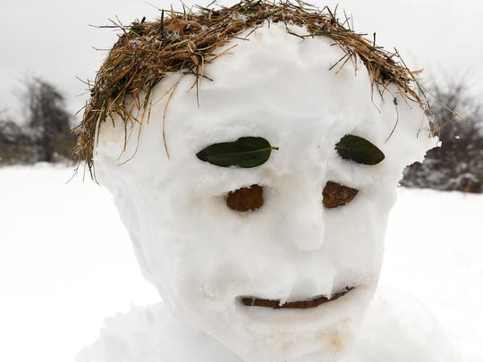 A snow lady crafted by hotel guest Taylor Stockum and front desk clerk Chase Rosensohn uses grass for hair, leaves for eyebrows, rocks for eyes and a stick for the mouth. Their creation stands outside Quality Inn & Suites in Staunton on Wednesday, March 21, 2018.