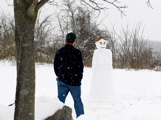 An employee ventures out to look at a snow lady crafted by hotel guest Taylor Stockum and front desk clerk Chase Rosensohn outside Quality Inn & Suites in Staunton on Wednesday, March 21, 2018.