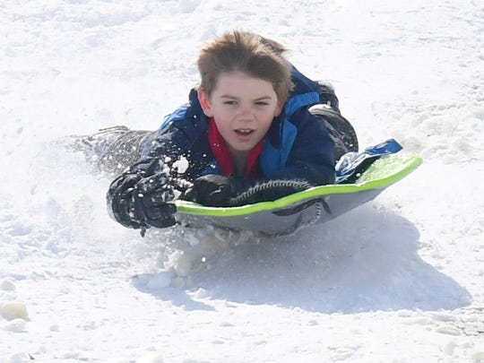 A young sledder holds on as he makes a run down a snow covered hill on the campus of Mary Baldwin University in Staunton on Thursday, March 22, 2018.
