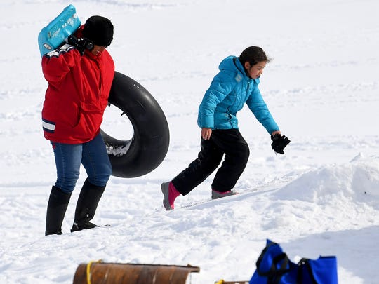 A pair of sledders make the trek back up a snow covered hill with tube in hand on the campus of Mary Baldwin University in Staunton on Thursday, March 22, 2018.