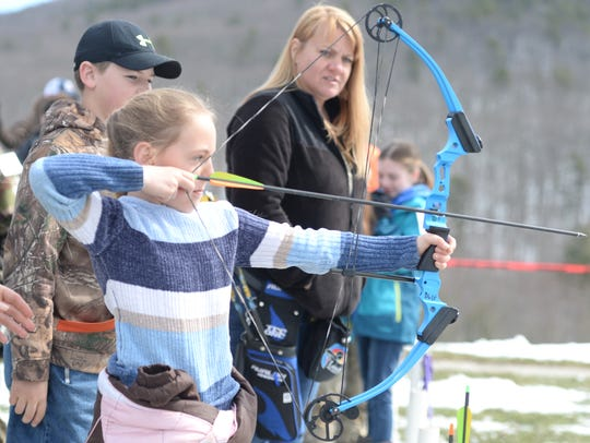 Brooklyn Moran, 8, aims for the target at the archery