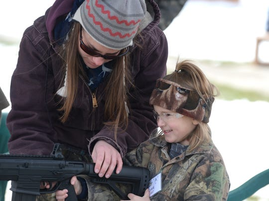 Meghan Rexrode helps 6-year-old Reece Weller at the