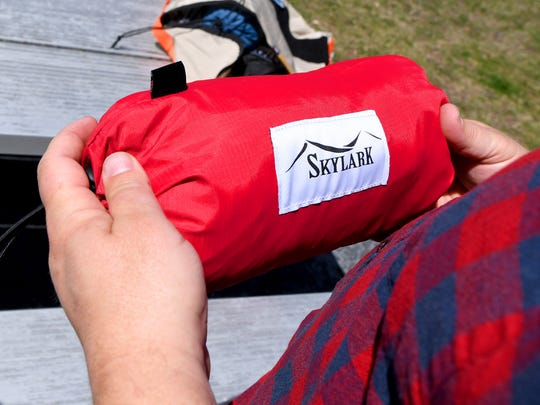 A bag branded with the Skylark Hammocks logo contains a hammock ready for use.