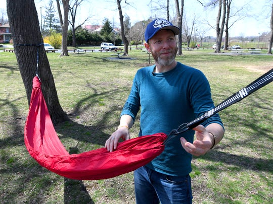 Co-owner Seth Blanchard of Skylark Hammocks sets up one of their hammocks to show how fast it can be down during an interview in Gypsy Hill Park on Friday, April 6, 2018.