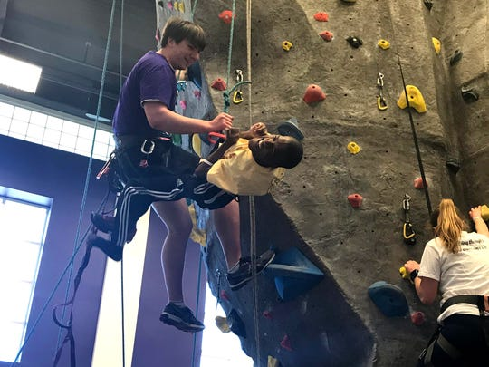 A JMU volunteer assists Donald Harms of Manassas on the climbing wall at Saturday's Overcoming Barriers Empowerment3 Ability Olympics. Harms, 21, has cerebral palsy.