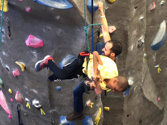 Michael Harms helps lower his son, Donald, from the climbing wall at JMU's Ability Olympics Saturday. Donald Harms has cerebral palsy.