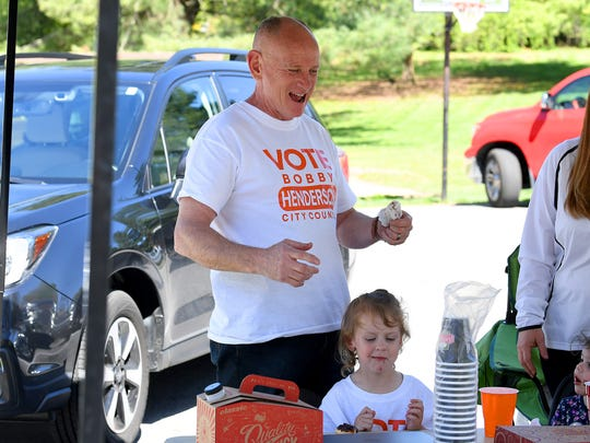 Bobby Henderson, candidate for Waynesboro city council, takes a moment to give his 2-year-old granddaughter, Spencer Lockridge, a snack. Henderson campaigns outside the Ward D polling place in Waynesboro on Tuesday, May 1, 2018.