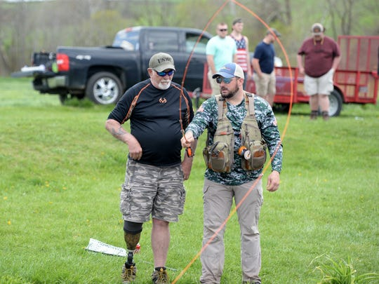 John Jenkins, right, gives Doug Massie some fly fishing tips Saturday afternoon in Ottobine. The two were taking part in a fishing event sponsored by Project Healing Waters.