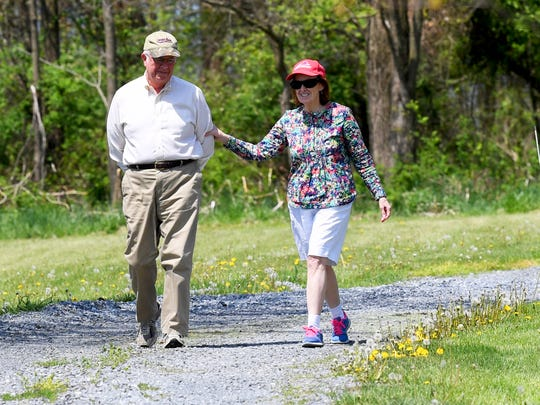 Carol Webb reaches out to her husband Patrick Webb as they share a moment while walking  Thursday, May 3, 2018. The couple like to go walking at least 3 times each week. Carol was diagnosed with Alzheimer's disease in November 2016.