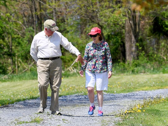 Patrick Webb reaches out to hold wife Carol Webb's hand as they walk on Thursday, May 3, 2018. The couple like to go walking at least 3 times each week. Carol was diagnosed with Alzheimer's disease in November 2016.