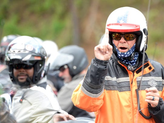 Kyle Petty holds up a single finger to indicate that only one rider at a time should pull out of Goshen Convenience Store as Petty's annual charity ride headed out for Bath County.