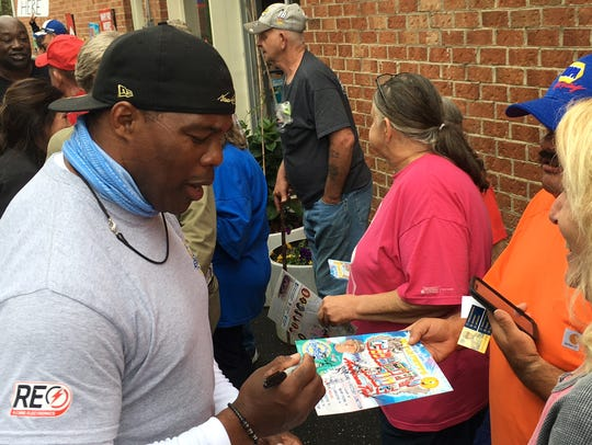 Former NFL player Herschel Walker signs an autograph