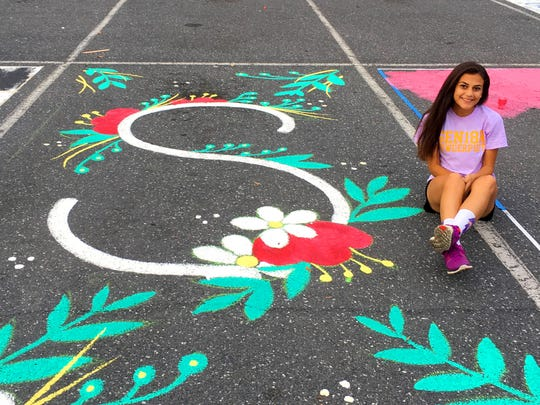 Senior Sabrina Munro is photographed with artwork she painted on her parking space outside Waynesboro High School.