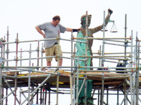 Doug Sheridan of Sunspots Studios stands on scaffolding with one hand resting on the shoulder of the statue of Lady of Justice on top Augusta County courthouse on Wednesday, May 16, 2018. Sheridan was contracted by Augusta County to replace the statue's scales which he completed. The statue remains surrounded by scaffolding as roof work continues to the building below.