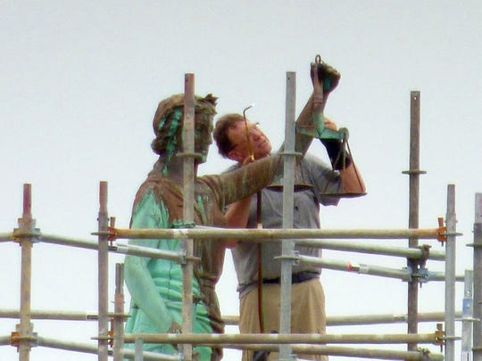 Doug Sheridan of Sunspots Studio replaces the scales of the Lady Justice statue on top Augusta County courthouse on Wednesday, May 16, 2018. Sheridan was contracted by Augusta County to replace the statue's scales which he completed. The statue remains surrounded by scaffolding as roof work continues to the building below.