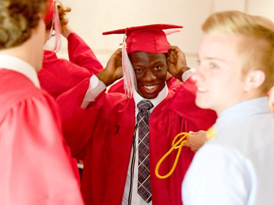 Graduate Joshua Akinwumi slips on his graduation cap as he prepares before the start of commencement exercises at Riverheads High School on Friday night, May 18, 2018.