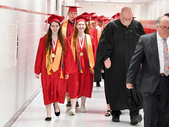 Valedictorian Olivia Katelynd Hathaway and salutatorian Mia Erin Kyler walk together alongside principal Max Lowe. They walk towards the gym where Riverheads High School commencement exercises will occur Friday night, May 18, 2018.