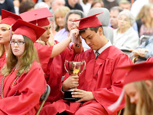 Graduate George William Theiss looks down at he school service award he just received as another graduate adjusts his cap. Riverheads High School held its commencement exercises at the school Friday night, May 18, 2018.