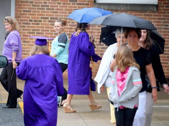 A graduate uses an umbrella as protection against a
