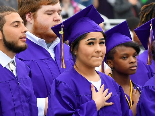 Graduates have hands over their hearts as the national